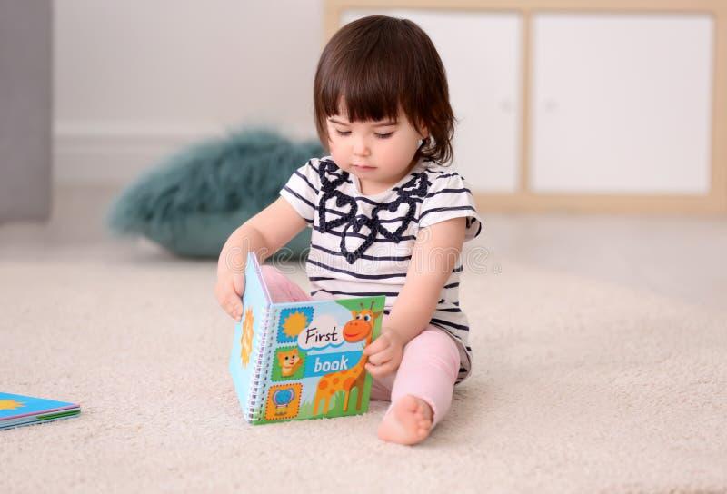 Χαριτωμένο κοριτσάκι με τη συνεδρίαση βιβλίων στο πάτωμα στοκ εικόνες