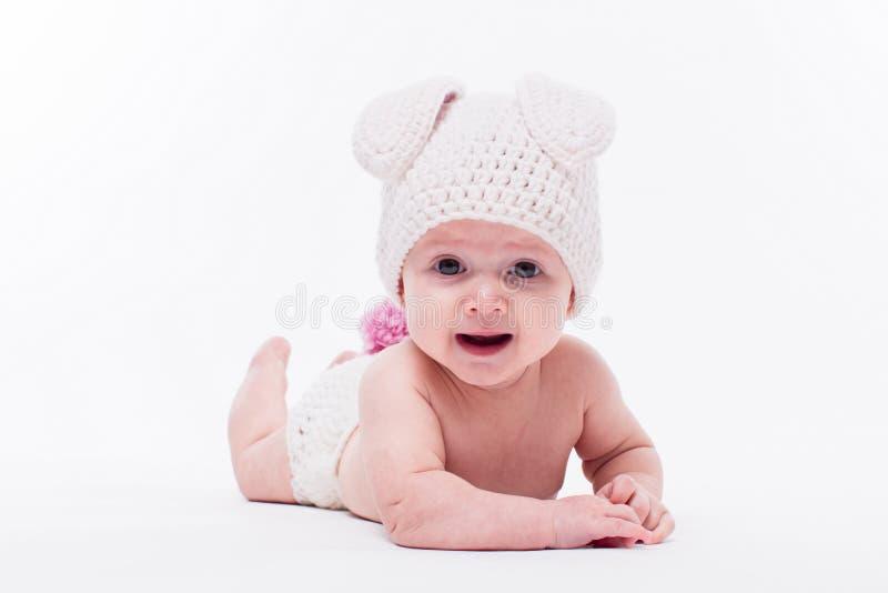 Χαριτωμένο κοριτσάκι που βρίσκεται γυμνό σε ένα άσπρο υπόβαθρο που φορά ένα καπέλο ι στοκ εικόνα