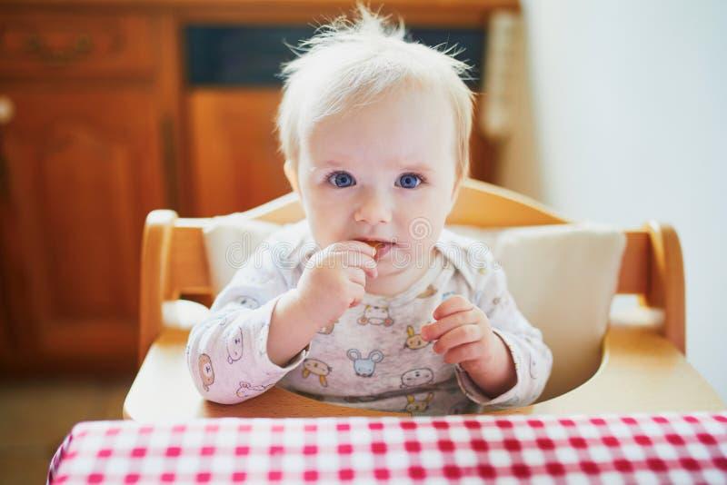 Χαριτωμένο κοριτσάκι που ταΐζεται με τα τρόφιμα δάχτυλων στην κουζίνα στοκ εικόνες
