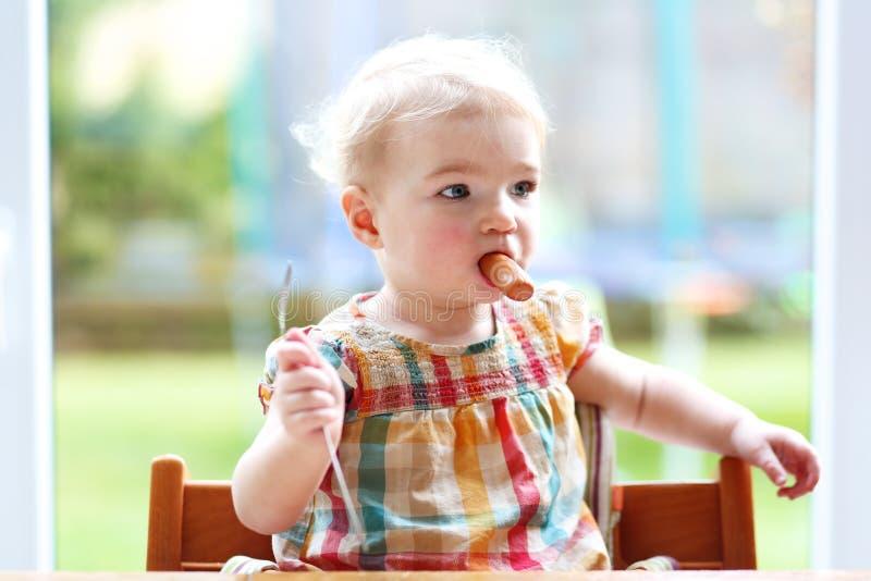 Χαριτωμένο κοριτσάκι που τρώει το λουκάνικο από το δίκρανο στοκ φωτογραφίες