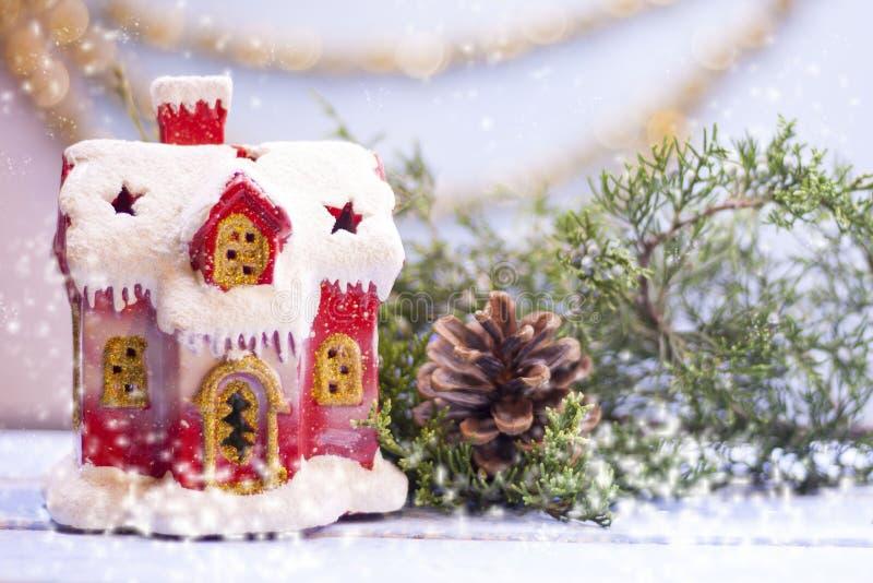 Χαριτωμένο κόκκινο χιονισμένο σπίτι με τα παράθυρα δίπλα σε έναν κωνοφόρο κλάδο και μια πρόσκρουση σε ένα ανοικτό μπλε υπόβαθρο μ στοκ εικόνα με δικαίωμα ελεύθερης χρήσης