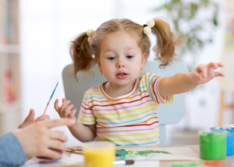 Χαριτωμένο λίγο κορίτσι μικρών παιδιών στο ριγωτά πουκάμισο και το πόνι παρακολουθεί τα χρώματα στην κατηγορία τέχνης στοκ φωτογραφίες με δικαίωμα ελεύθερης χρήσης