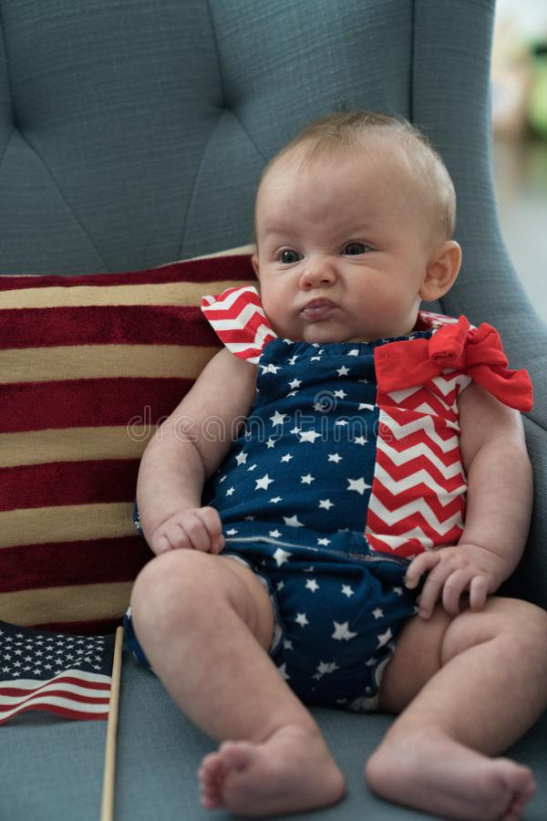 Χαριτωμένο λίγο μωρό έντυσε σε μια πατριωτική ΑΜΕΡΙΚΑΝΙΚΗ εξάρτηση στοκ φωτογραφία