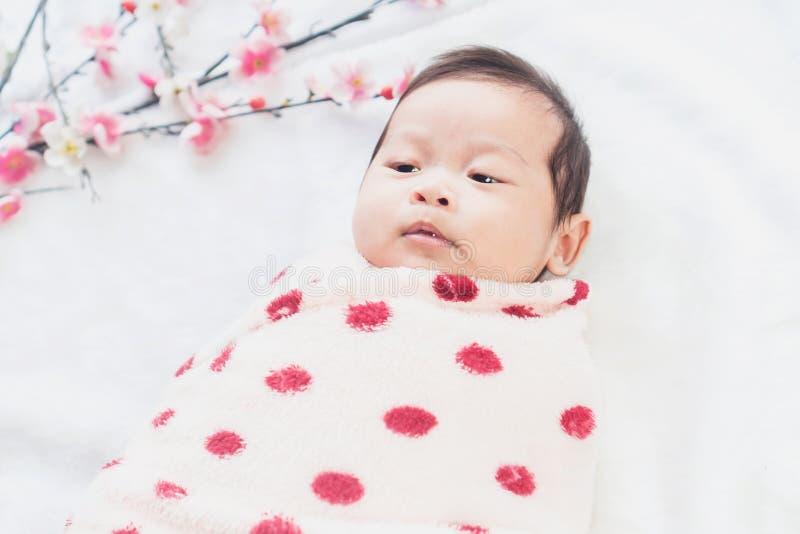 Χαριτωμένο λίγο μωρό βρίσκεται σε ένα άσπρο ύφασμα και τυλιγμένος στο πάπλωμα, κοιτάζοντας γύρω Στην άσπρη ανασκόπηση στοκ εικόνες