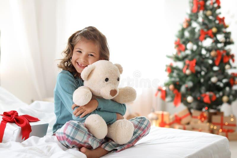 Χαριτωμένο λίγο παιδί με το παιχνίδι αντέχει και το κιβώτιο δώρων Χριστουγέννων στοκ φωτογραφία με δικαίωμα ελεύθερης χρήσης