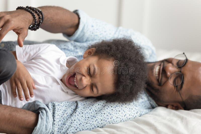 Χαριτωμένο λατρευτό παιχνίδι γέλιου γιων παιδιών αφροαμερικάνων με τον πατέρα στοκ φωτογραφία με δικαίωμα ελεύθερης χρήσης