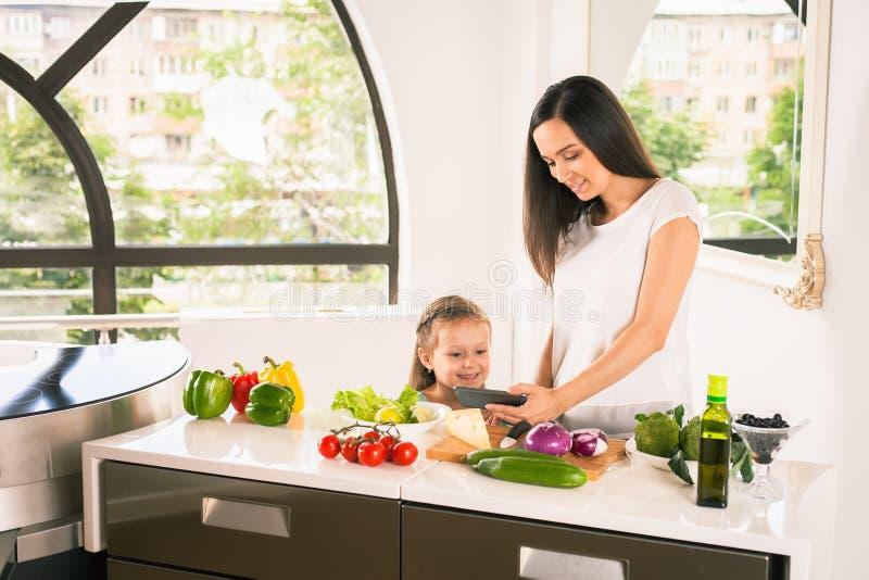 Χαριτωμένο μαγείρεμα μικρών κοριτσιών με τη μητέρα της στην κουζίνα στοκ φωτογραφίες με δικαίωμα ελεύθερης χρήσης