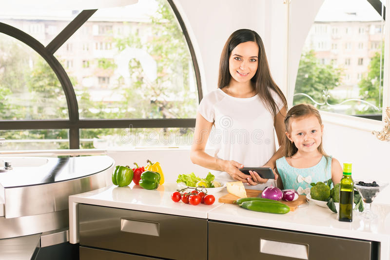 Χαριτωμένο μαγείρεμα μικρών κοριτσιών με τη μητέρα της στην κουζίνα στοκ εικόνες