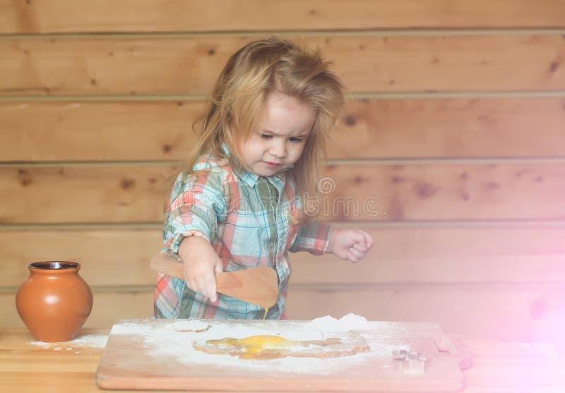 Χαριτωμένο μαγείρεμα παιδιών με τη ζύμη, το αλεύρι, το αυγό και το κύπελλο στοκ εικόνα με δικαίωμα ελεύθερης χρήσης