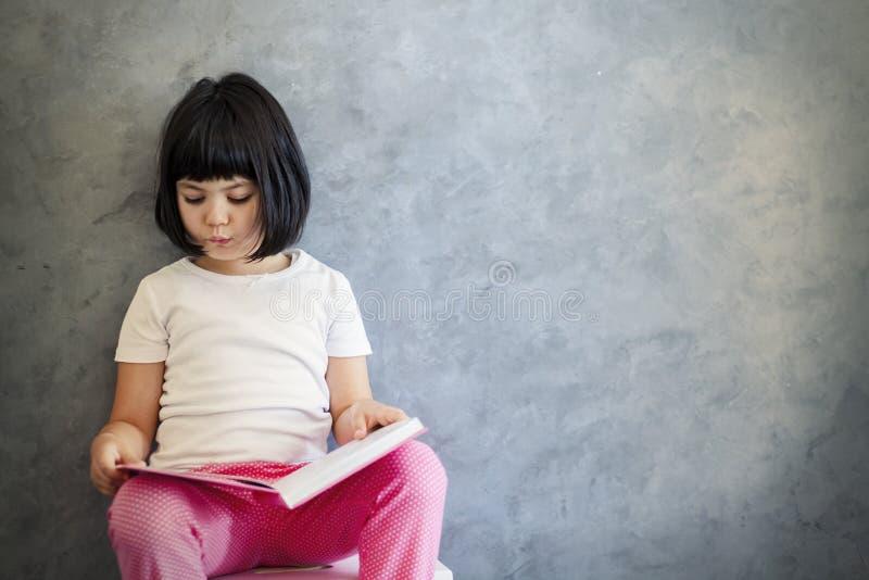 Χαριτωμένο μαύρο βιβλίο ανάγνωσης μικρών κοριτσιών τρίχας από τον τοίχο στοκ φωτογραφίες με δικαίωμα ελεύθερης χρήσης