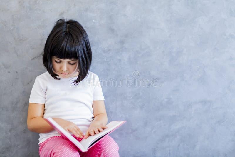 Χαριτωμένο μαύρο βιβλίο ανάγνωσης μικρών κοριτσιών τρίχας από τον τοίχο στοκ εικόνα με δικαίωμα ελεύθερης χρήσης