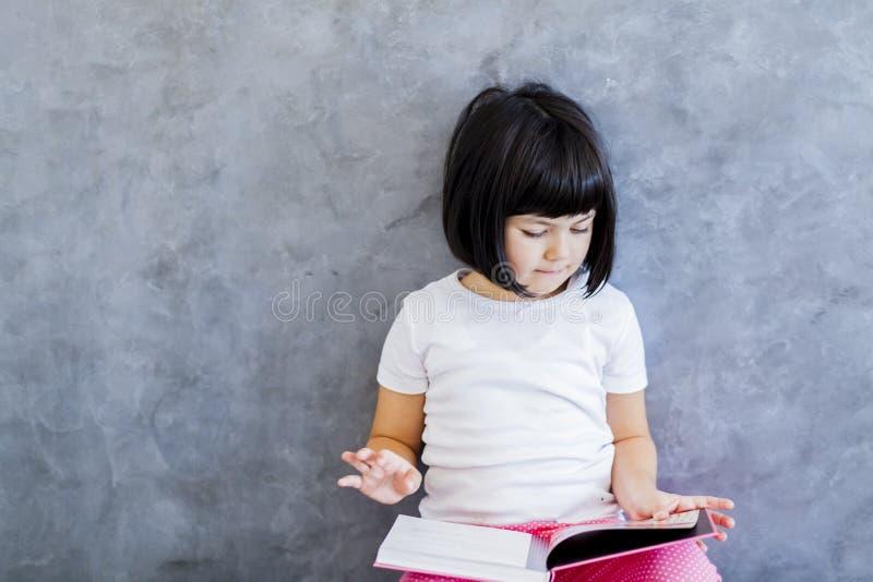 Χαριτωμένο μαύρο βιβλίο ανάγνωσης μικρών κοριτσιών τρίχας από τον τοίχο στοκ φωτογραφίες
