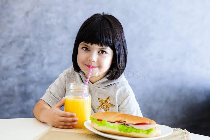 Χαριτωμένο μαύρο μικρό κορίτσι τρίχας που έχει το πρόγευμα και που πίνει το πορτοκάλι στοκ φωτογραφίες