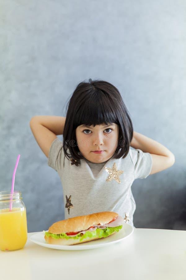 Χαριτωμένο μαύρο μικρό κορίτσι τρίχας που έχει το πρόγευμα και που πίνει το πορτοκάλι στοκ εικόνες με δικαίωμα ελεύθερης χρήσης
