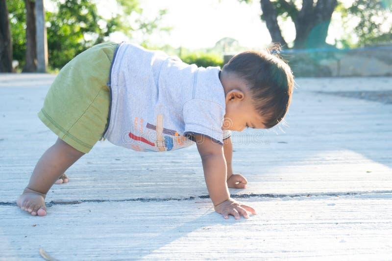 Χαριτωμένο μικρό ασιατικό μικρό σκαμπό μωρό στο πάτωμα στοκ φωτογραφίες