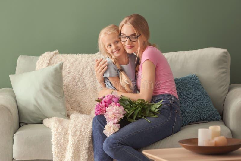 Χαριτωμένο μικρό κορίτσι και η μητέρα της με τα όμορφα λουλούδια που κάθονται στον καναπέ στο σπίτι στοκ φωτογραφίες