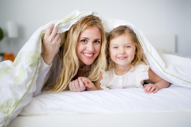 Χαριτωμένο μικρό κορίτσι και η μητέρα της που βρίσκονται σε ένα κρεβάτι στοκ εικόνες