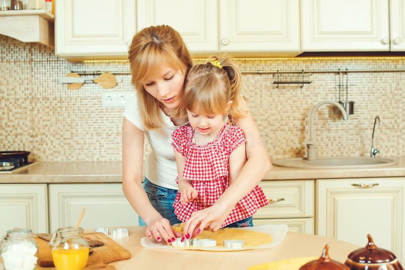 Χαριτωμένο μικρό κορίτσι και η μητέρα της που προετοιμάζουν τα μπισκότα που χρησιμοποιούν τους κόπτες μπισκότων, που καλλιεργούντ στοκ φωτογραφίες