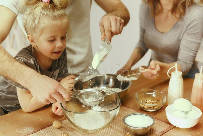 Χαριτωμένο μικρό κορίτσι και οι όμορφοι γονείς της που προετοιμάζουν τη ζύμη για το κέικ στην κουζίνα στο σπίτι στοκ εικόνα με δικαίωμα ελεύθερης χρήσης