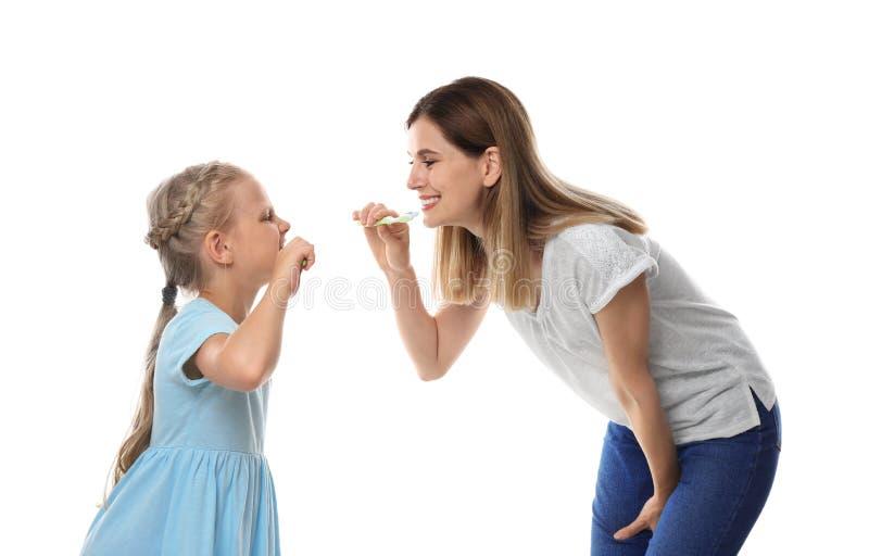Χαριτωμένο μικρό κορίτσι και τα δόντια βουρτσίσματος μητέρων της στο άσπρο υπόβαθρο στοκ φωτογραφία με δικαίωμα ελεύθερης χρήσης