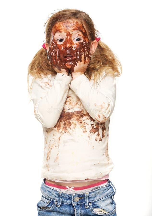 Χαριτωμένο μικρό κορίτσι με καλυμμένο το σοκολάτα πρόσωπο στοκ εικόνα