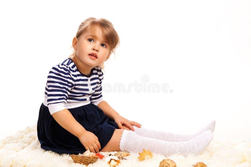 Χαριτωμένο μικρό κορίτσι με τα θαλασσινά κοχύλια στοκ φωτογραφίες με δικαίωμα ελεύθερης χρήσης