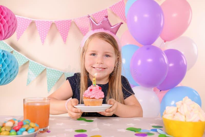 Χαριτωμένο μικρό κορίτσι με τα νόστιμα γενέθλια εορτασμού cupcake στο σπίτι στοκ εικόνα