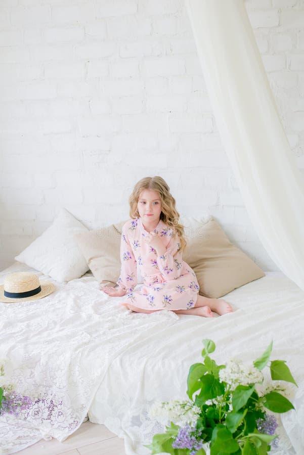 Χαριτωμένο μικρό κορίτσι με τα ξανθά μαλλιά σε ένα όμορφο φόρεμα σε ένα στούντιο άνοιξη με την πασχαλιά στοκ φωτογραφία με δικαίωμα ελεύθερης χρήσης