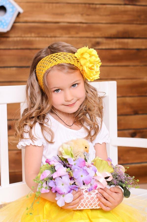Χαριτωμένο μικρό κορίτσι με τα λουλούδια και το ζωντανό κοτόπουλο στοκ εικόνες με δικαίωμα ελεύθερης χρήσης