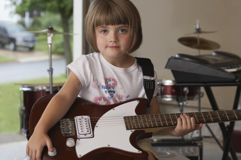 Χαριτωμένο μικρό κορίτσι με την κιθάρα στο γκαράζ στοκ φωτογραφία