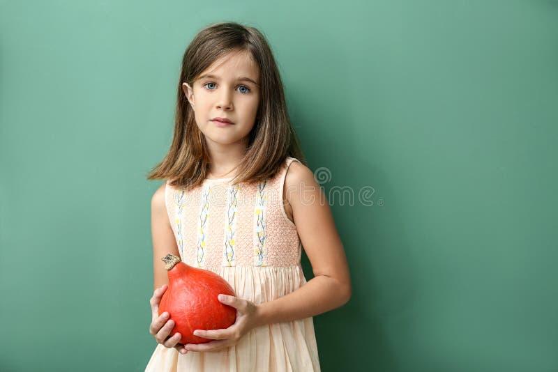 Χαριτωμένο μικρό κορίτσι με την κολοκύθα στο υπόβαθρο χρώματος στοκ φωτογραφία με δικαίωμα ελεύθερης χρήσης