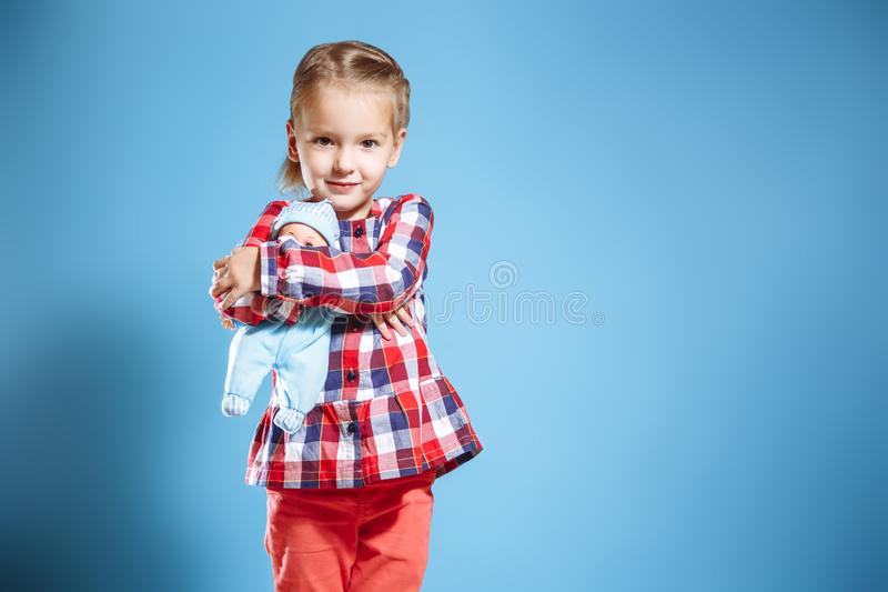 Χαριτωμένο μικρό κορίτσι με την κούκλα στο μπλε υπόβαθρο στοκ φωτογραφίες με δικαίωμα ελεύθερης χρήσης
