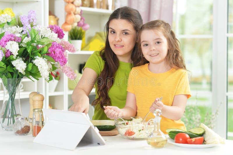 Χαριτωμένο μικρό κορίτσι με τη μητέρα της που μαγειρεύει από κοινού στοκ φωτογραφία με δικαίωμα ελεύθερης χρήσης