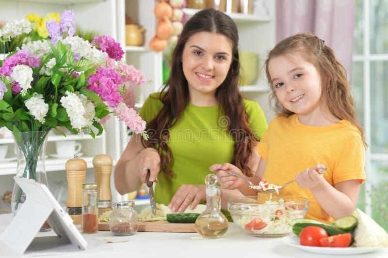Χαριτωμένο μικρό κορίτσι με τη μητέρα της που μαγειρεύει από κοινού στοκ φωτογραφία