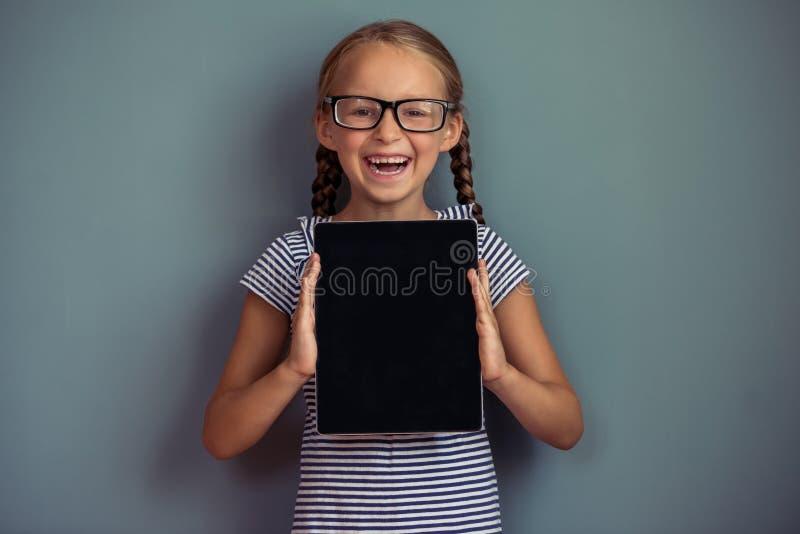 Χαριτωμένο μικρό κορίτσι με τη συσκευή στοκ εικόνες