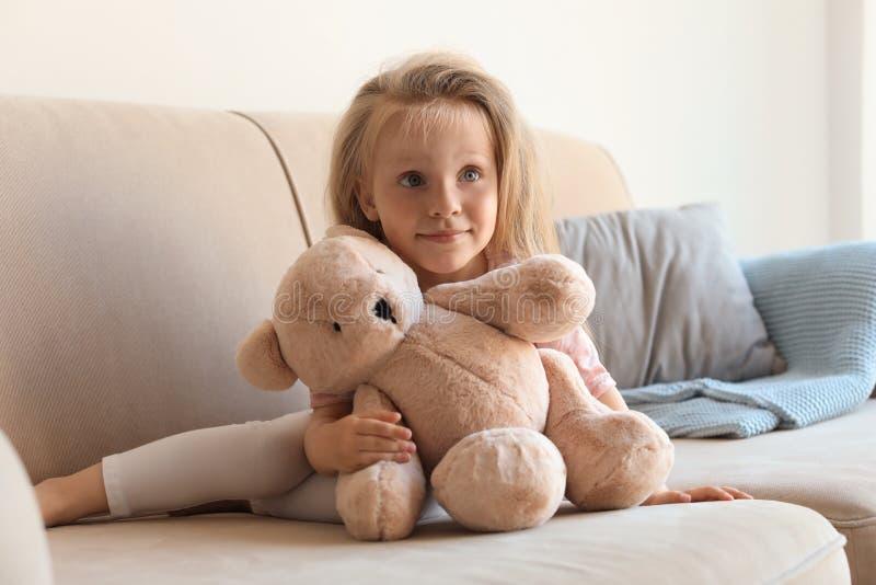 Χαριτωμένο μικρό κορίτσι με τη teddy αρκούδα στον καναπέ στοκ εικόνα