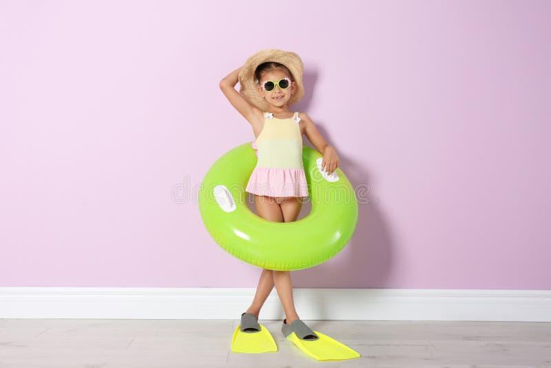 Χαριτωμένο μικρό κορίτσι με το διογκώσιμο δαχτυλίδι που φορά τα βατραχοπέδιλα στοκ φωτογραφία