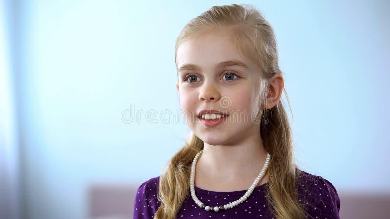 Χαριτωμένο μικρό κορίτσι με το κόσμημα περιδεραίων που κοιτάζει στον καθρέφτη, που απολαμβάνει την εξάρτηση στοκ φωτογραφία