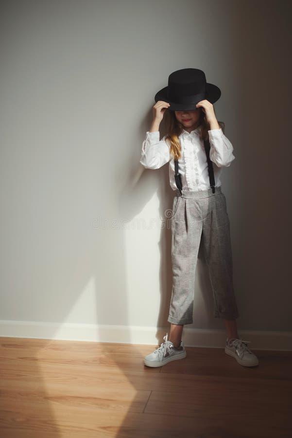 Χαριτωμένο μικρό κορίτσι με το μαύρο καπέλο στο σπίτι στοκ φωτογραφία