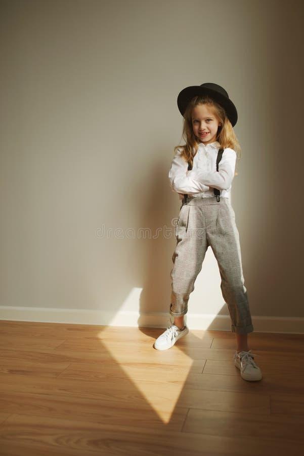 Χαριτωμένο μικρό κορίτσι με το μαύρο καπέλο στο σπίτι στοκ φωτογραφίες με δικαίωμα ελεύθερης χρήσης