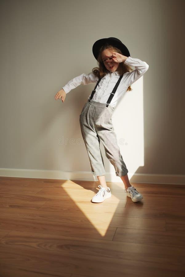 Χαριτωμένο μικρό κορίτσι με το μαύρο καπέλο στο σπίτι στοκ φωτογραφία με δικαίωμα ελεύθερης χρήσης