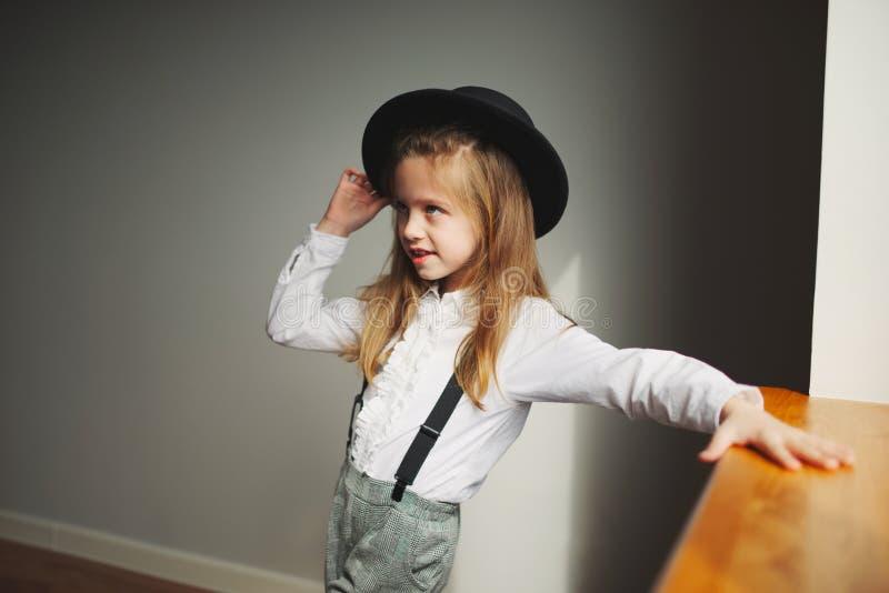 Χαριτωμένο μικρό κορίτσι με το μαύρο καπέλο στο σπίτι στοκ εικόνες