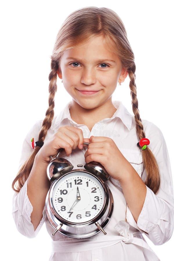 Χαριτωμένο μικρό κορίτσι με το ξυπνητήρι που απομονώνεται στο άσπρο υπόβαθρο στοκ εικόνες