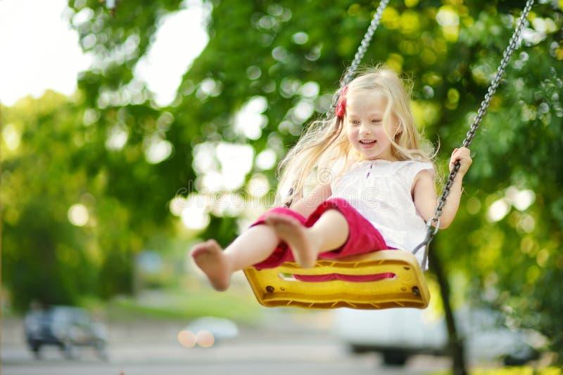 Χαριτωμένο μικρό κορίτσι που έχει τη διασκέδαση σε μια παιδική χαρά υπαίθρια τη θερμή θερινή ημέρα στοκ εικόνες