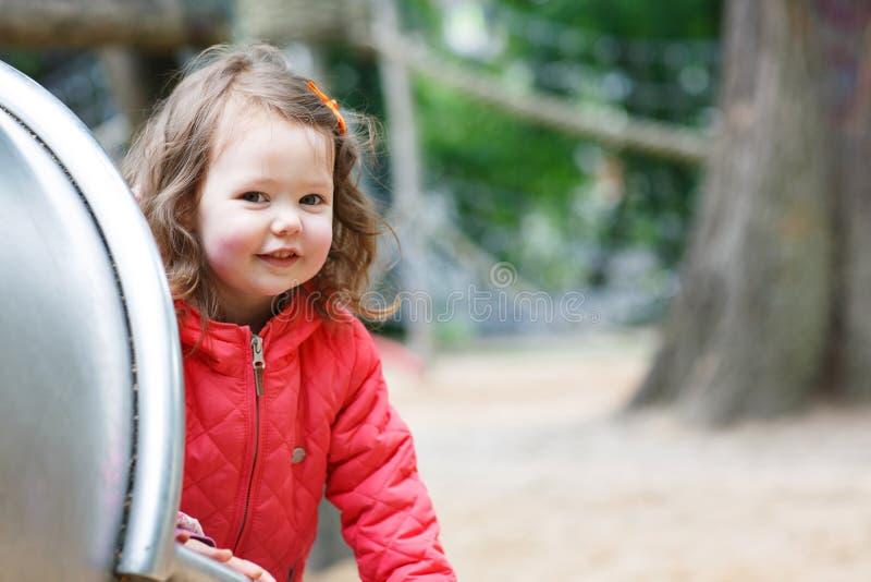Χαριτωμένο μικρό κορίτσι που έχει τη διασκέδαση στην παιδική χαρά στοκ εικόνα