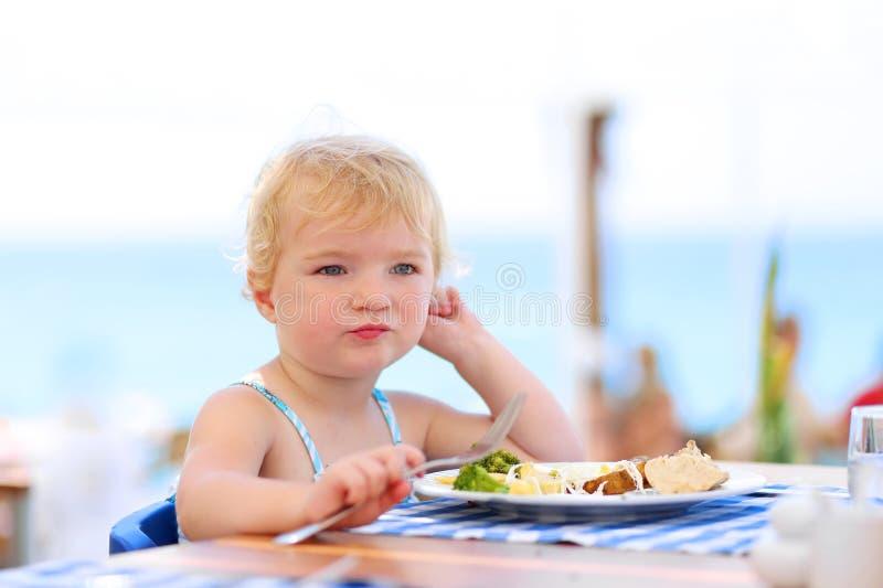 Χαριτωμένο μικρό κορίτσι που έχει το μεσημεριανό γεύμα στο εστιατόριο θερέτρου στοκ εικόνες