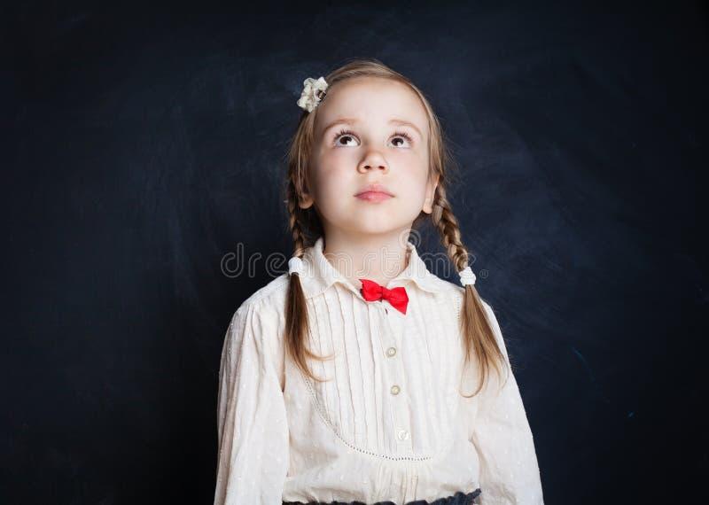 Χαριτωμένο μικρό κορίτσι που ανατρέχει στον πίνακα στοκ εικόνες με δικαίωμα ελεύθερης χρήσης