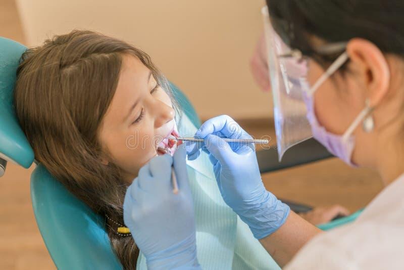 Χαριτωμένο μικρό κορίτσι που βρίσκεται σε μια καρέκλα οδοντιάτρων και που χαμογελά στη κάμερα ενώ η διεύθυνση μια εξέταση στοματι στοκ εικόνα