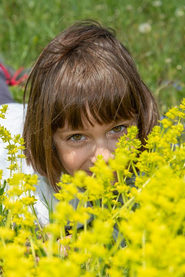 Χαριτωμένο μικρό κορίτσι που βρίσκεται στη χλόη και τα λουλούδια και το γέλιο στοκ εικόνες