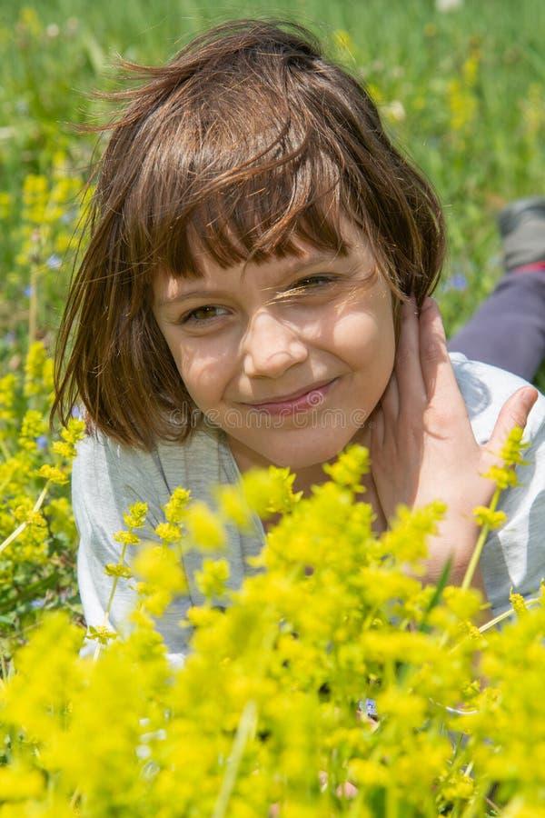 Χαριτωμένο μικρό κορίτσι που βρίσκεται στη χλόη και τα λουλούδια και το γέλιο στοκ φωτογραφίες